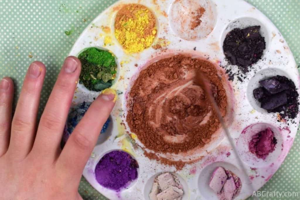 mixing orange eyeshadow with rubbing alcohol in a mixing tray with other rainbow eyeshadow colors around it