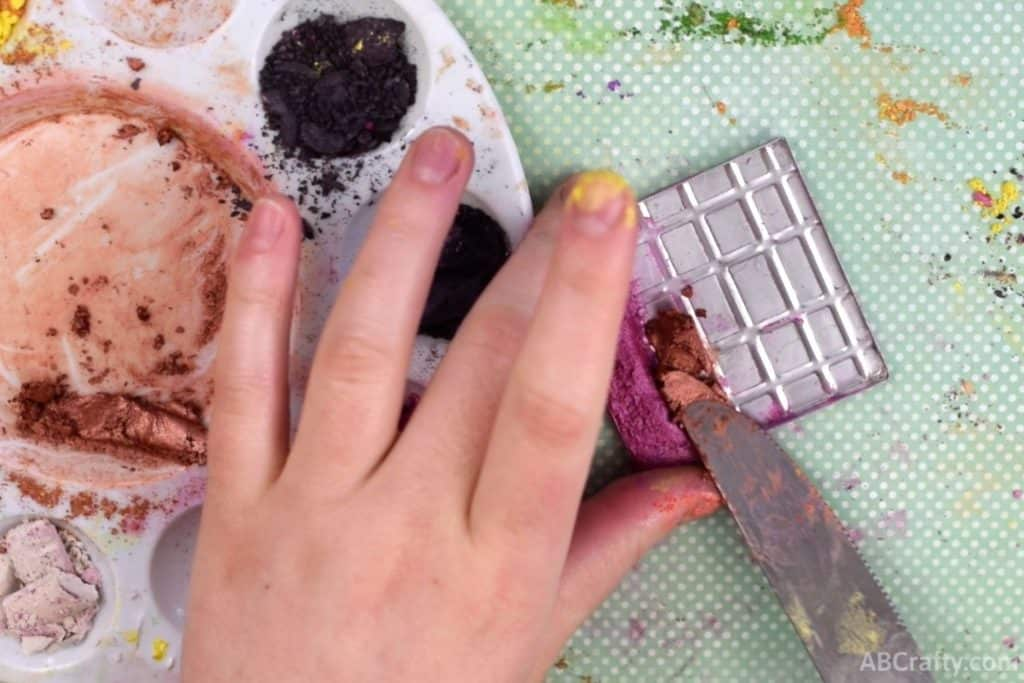 using a knife to put orange shimmer eyeshadow paste next to pink