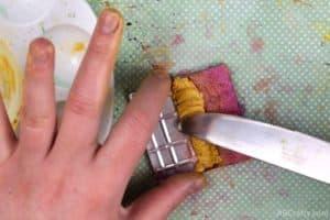 putting yellow shimmer eyeshadow paste into a tin next to orange