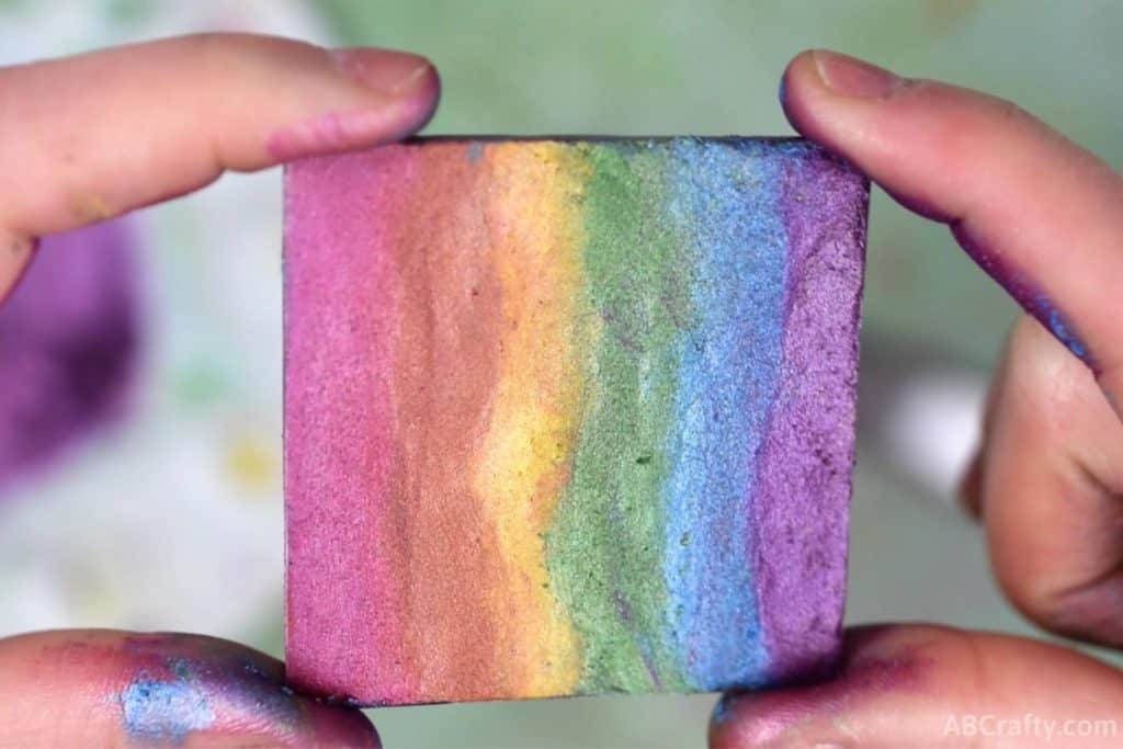 holding a finished diy rainbow highlighter that's in the shape of a square