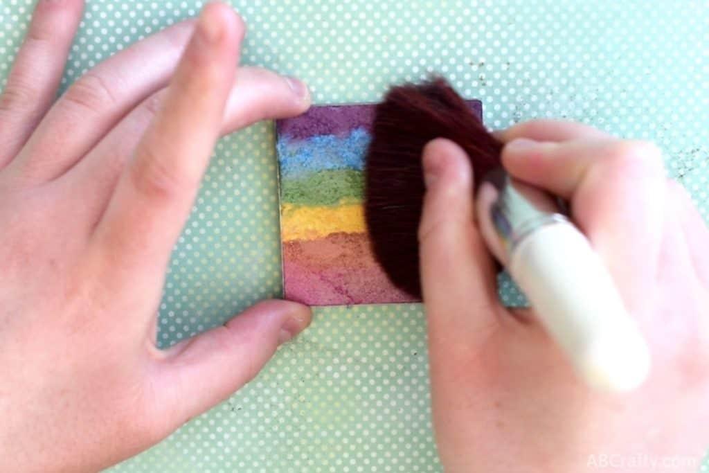 wiping a big fluffy makeup brush across a diy rainbow highler