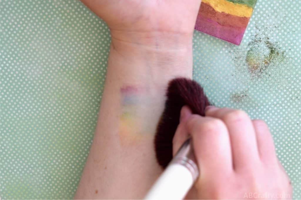 wiping rainbow makeup across the forearm with a makeup brush