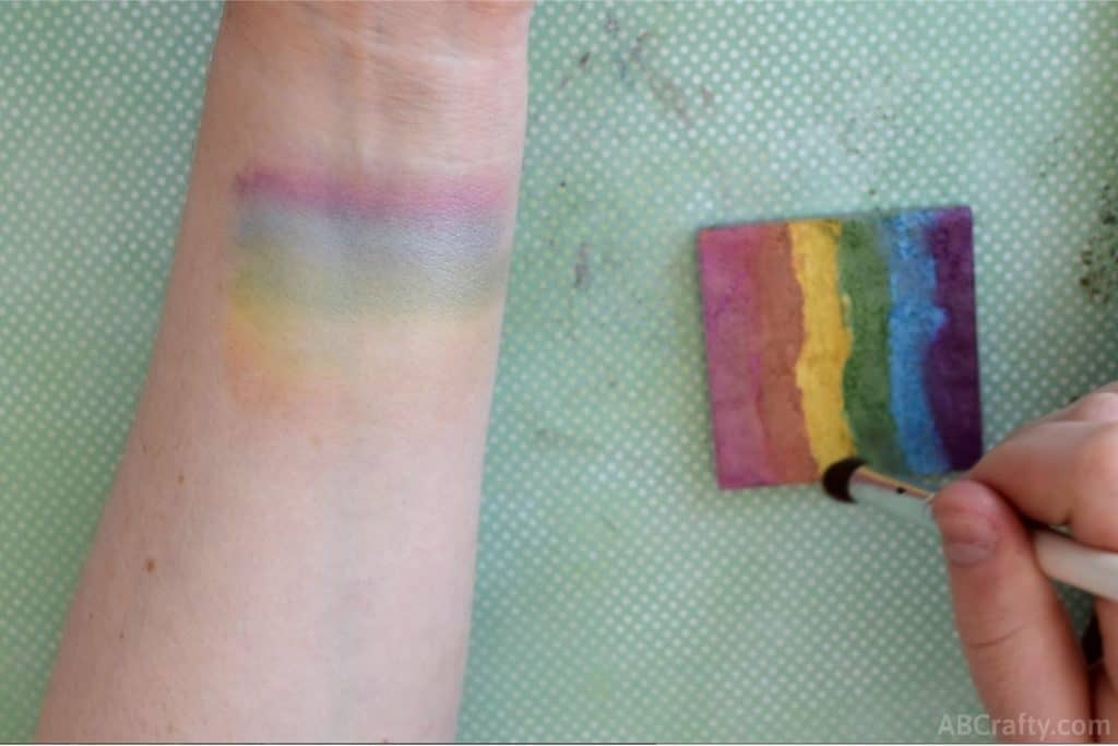 wrist with rainbow makeup on it while dipping a makeup brush into a diy rainbow highlighter