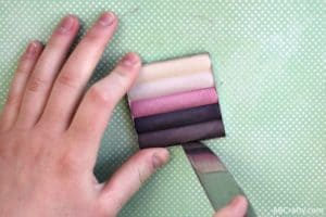 using a knife to remove purple shimmer eyeshadow from an eyeshadow tin