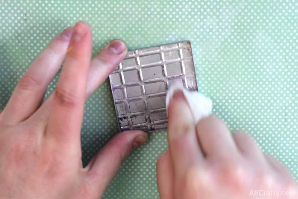 cleaning an eyeshadow tin with a paper towel