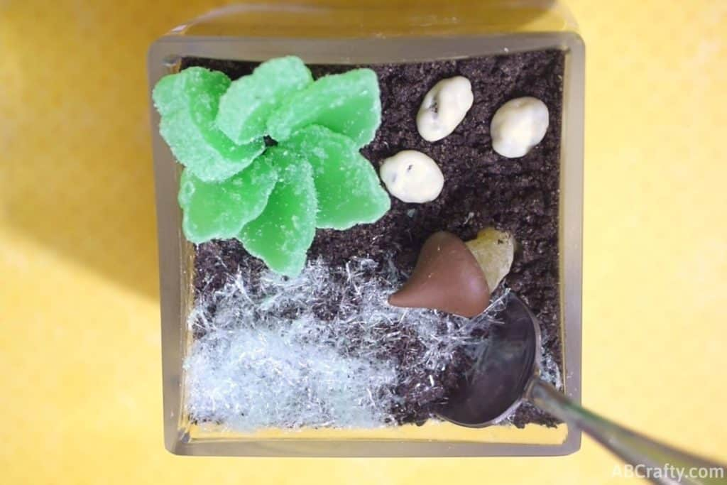 top view of edible terrarium with a spoon in the oreo dirt and showing the cotton candy grass, candy succulent, and chocolate rocks and mushroom