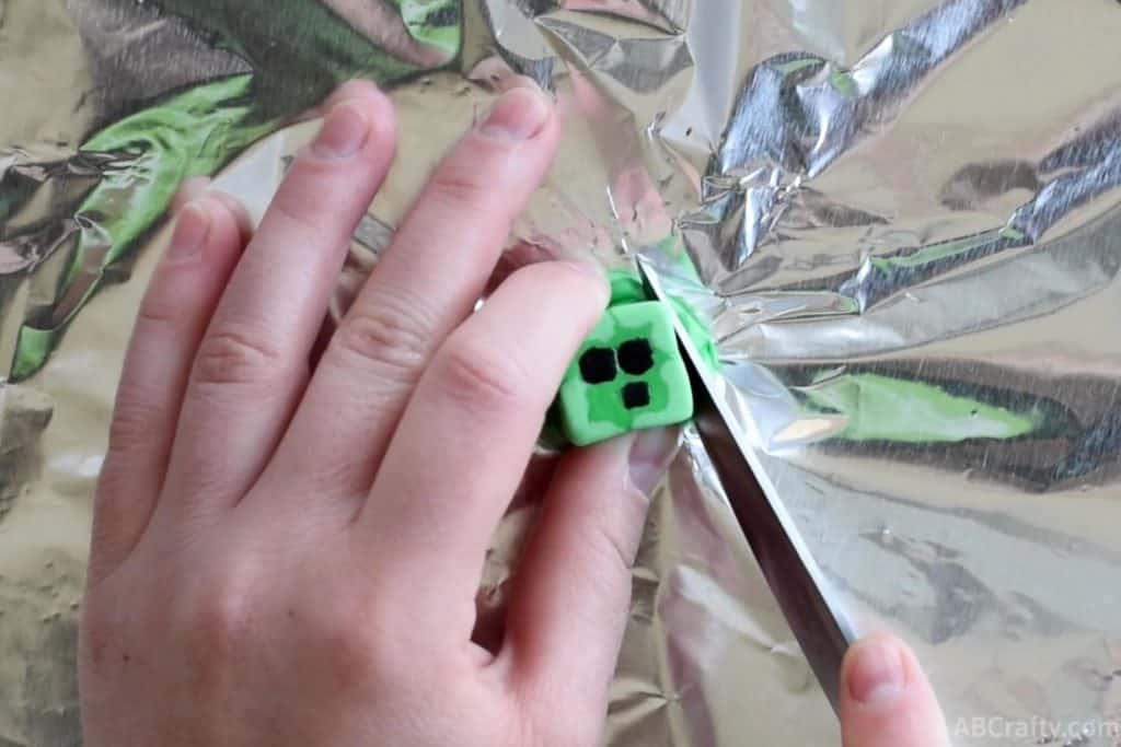 using a knife to cut off the edges of a minecraft eraser that looks like a slime chunk