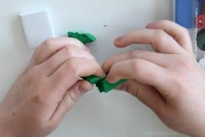 tearing off some green eraser clay from the creatibles diy eraser kit