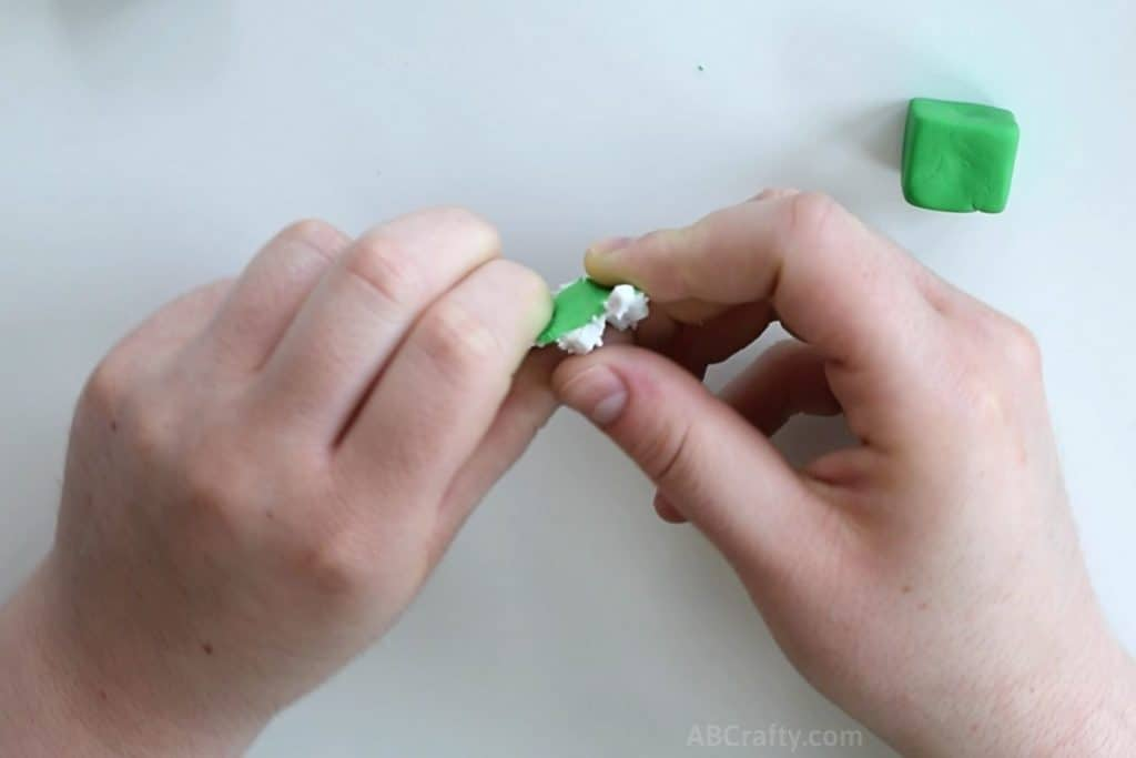 mixing a small amount of green clay with white clay with a green clay cube in the corner