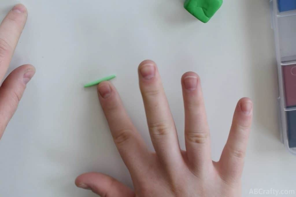 rolling a small green log of clay with an index finger