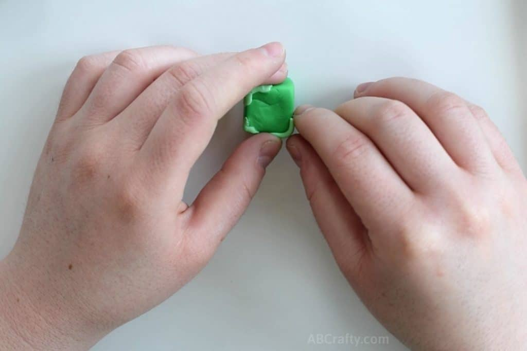 adding small strips of light green eraser clay to the corners of a green cube