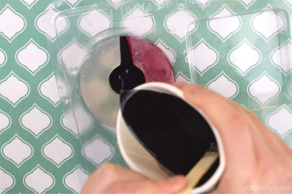 pouring melted black glycerin soap into the center of a pokeball shape in a plastic round soap mold