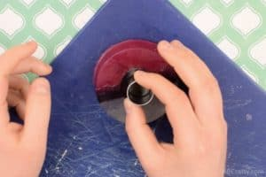 Using a circle cookie cutter to cut out the center button of a pokeball soap