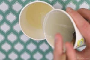 pouring melted clear glycerin soap from one paper cup into another