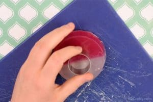 holding a small circle cookie cutter on top of a round soap that is half red and half white