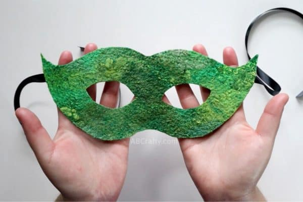 holding a finished green masquerade mask made out of wet felted handmade felt with black satin ribbon hanging from the sides