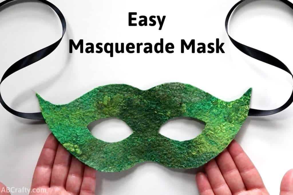 """hands holding a green masquerade mask made out of handmade felt with black ribbon hanging from the sides with the title """"easy masquerade mask"""""""