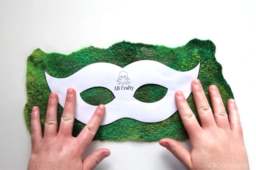 placing ab crafty masquerade mask template over green handmade felt