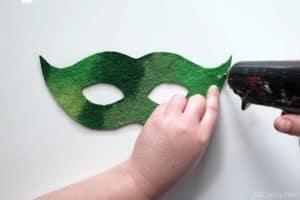 using a glue gun to put glue onto the edge of a green mask