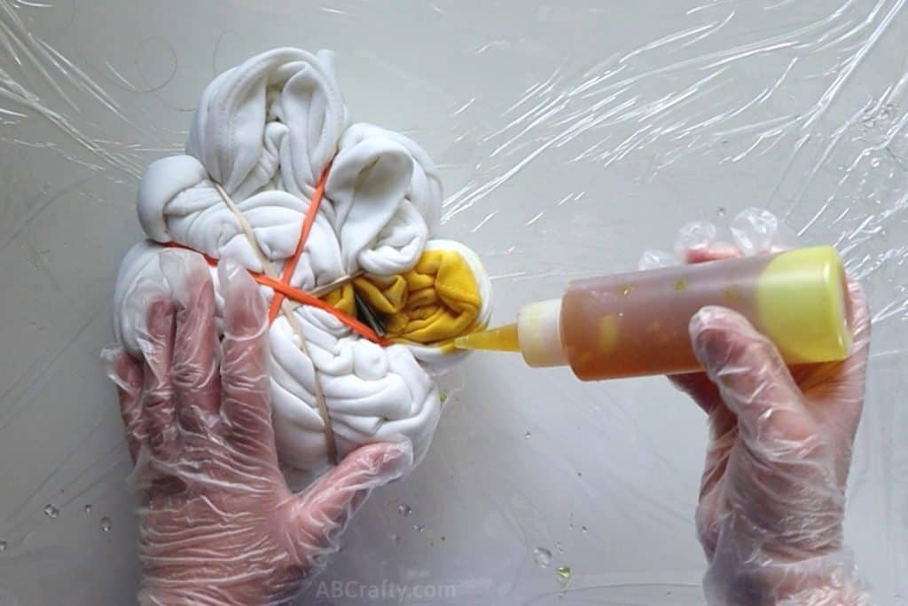 pouring yellow tie dye onto a section of a white sweatshirt in the shape of a spiral wrapped in rubber bands