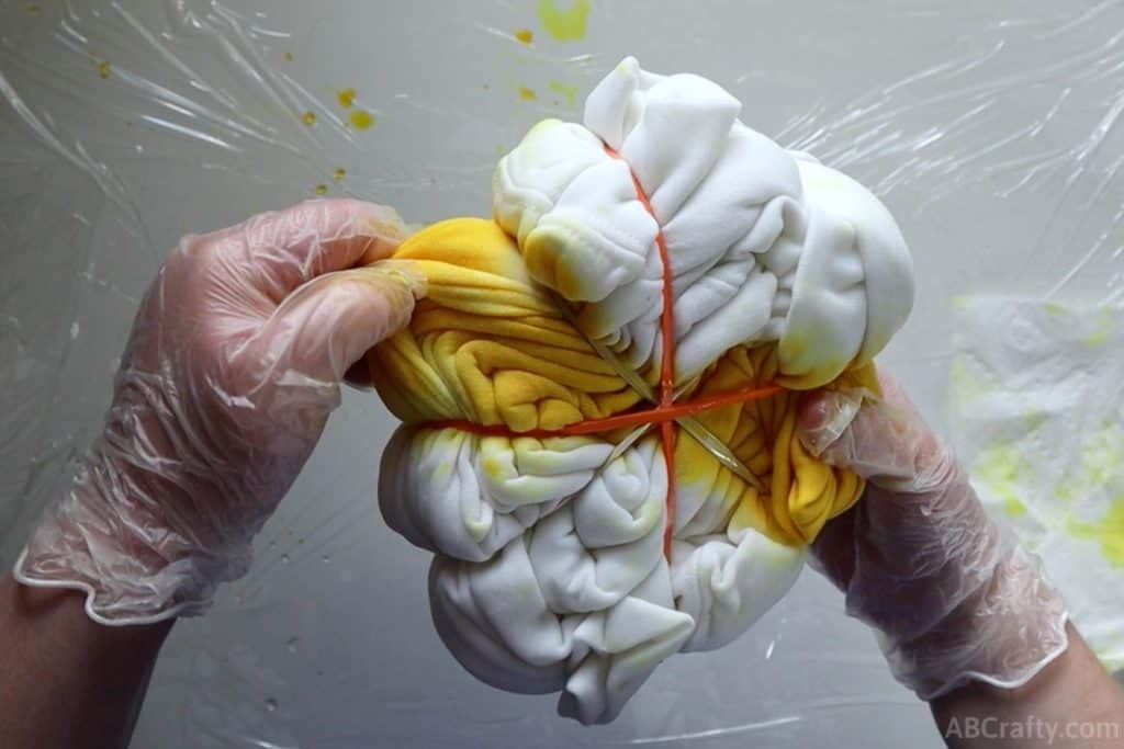 pulling apart the layers of a white sweatshirt that's been wrapped into a spiral and wrapped in rubber bands with two opposite sections covered in yellow tie dye