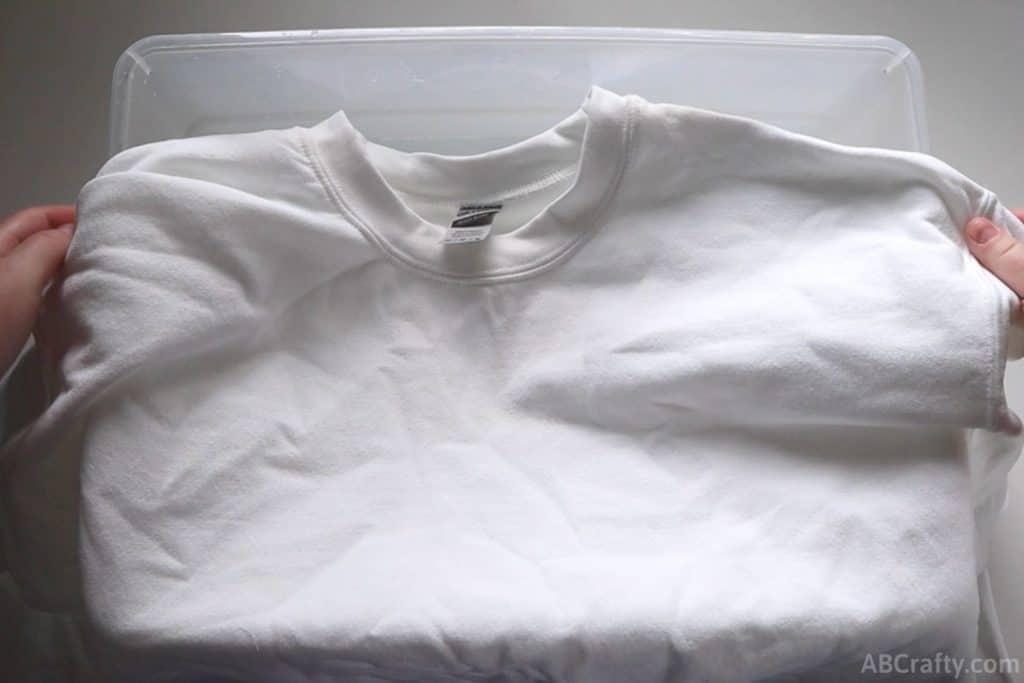 holding a plain white cotton sweatshirt over a plastic tub