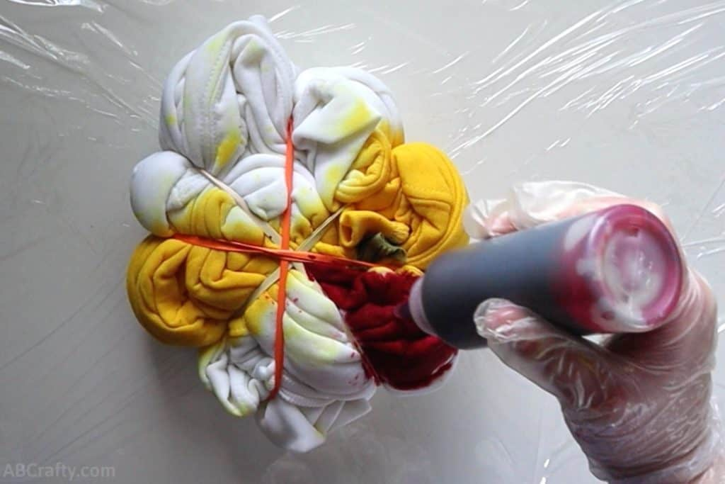pouring red tie dye into a section between rubber bands