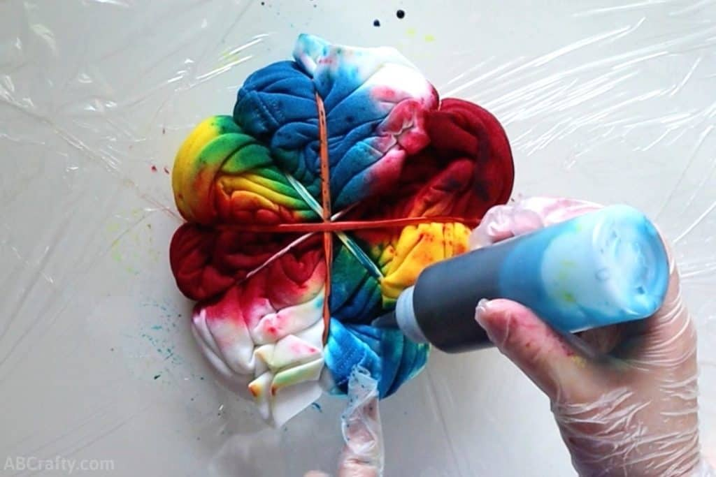 pouring blue tie dye onto a sweatshirt wrapped into a spiral with different primary colors on each section