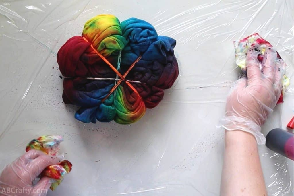 wiping dye off of plastic wrap next to a sweatshirt covered in rainbow tie dye