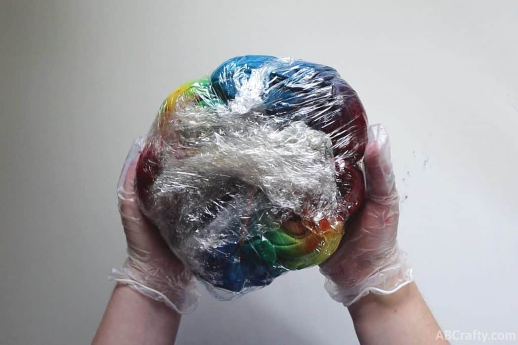 holding a wet sweatshirt covered in rainbow tie dye completely wrapped in plastic wrap