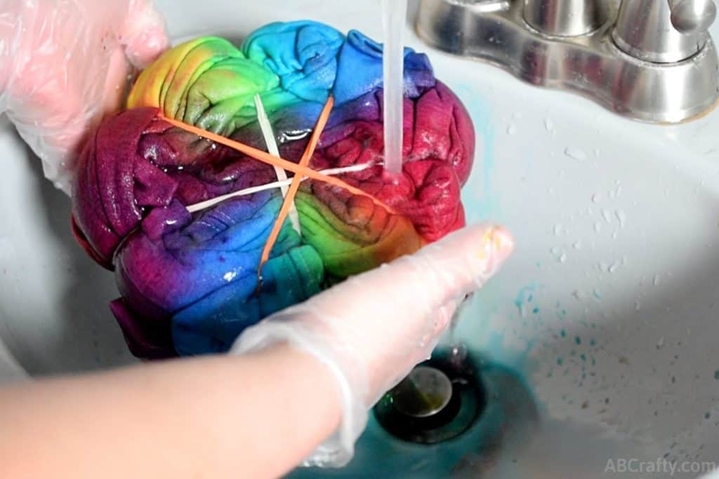 running a rainbow tie dye sweatshirt shaped in a spiral and covered in rubber bands under water so the dye washes out
