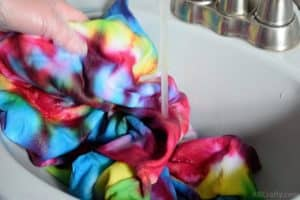 washing a rainbow tie dye sweatshirt under water