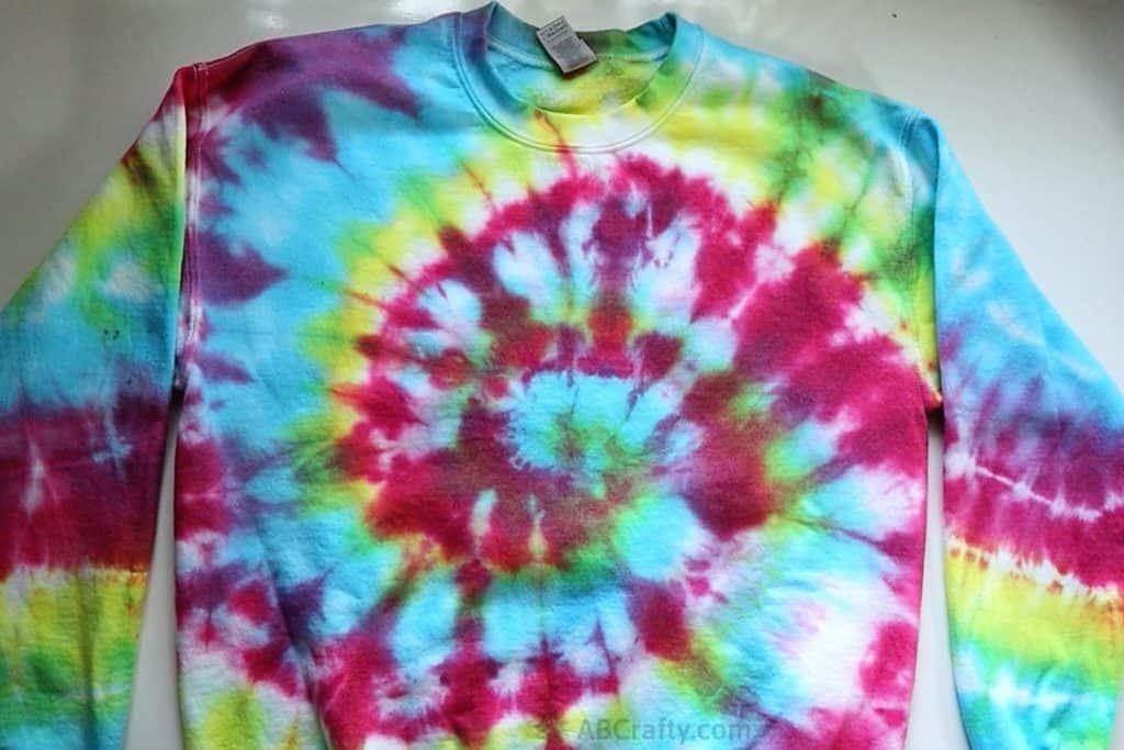 rainbow tie dye sweatshirt on a table with a spiral tie dye pattern