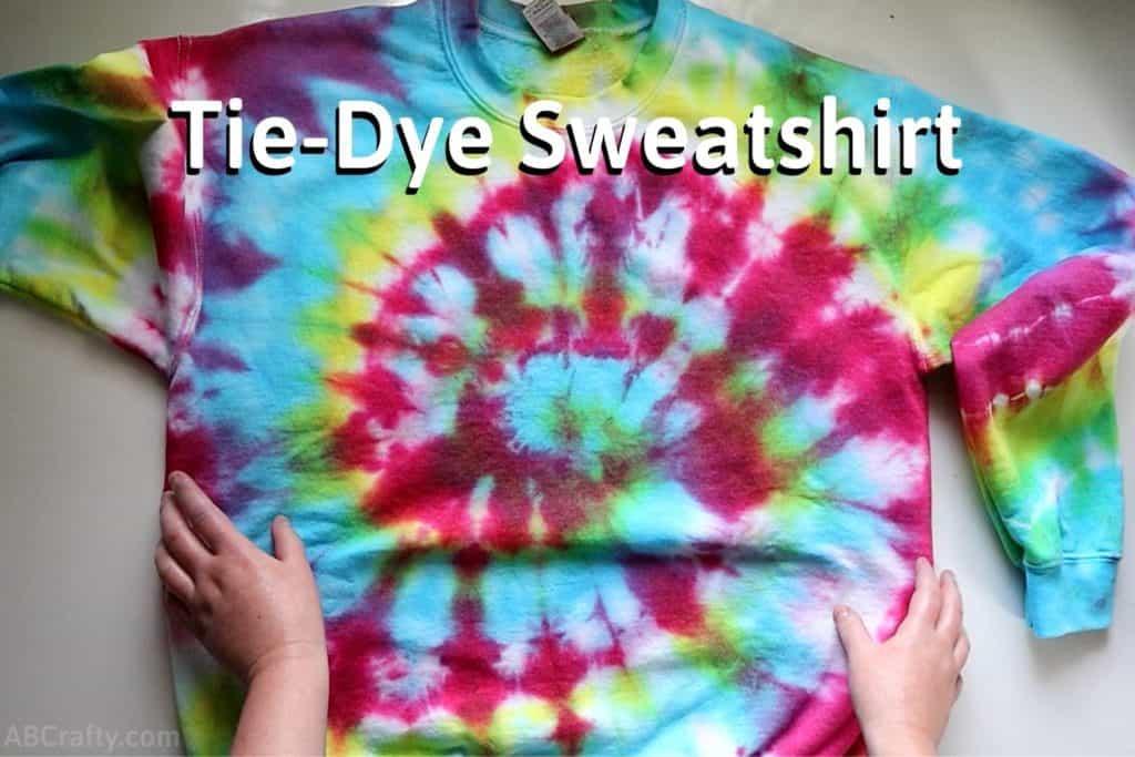 "touching a rainbow tie dye sweatshirt on a table with a spiral tie dye pattern with the title ""tie-dye sweatshirt"""