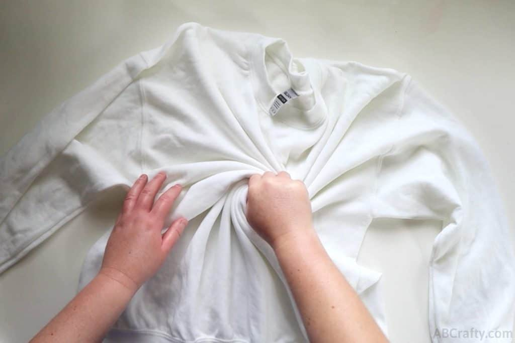 twisting the middle of white sweatshirt to make a spiral