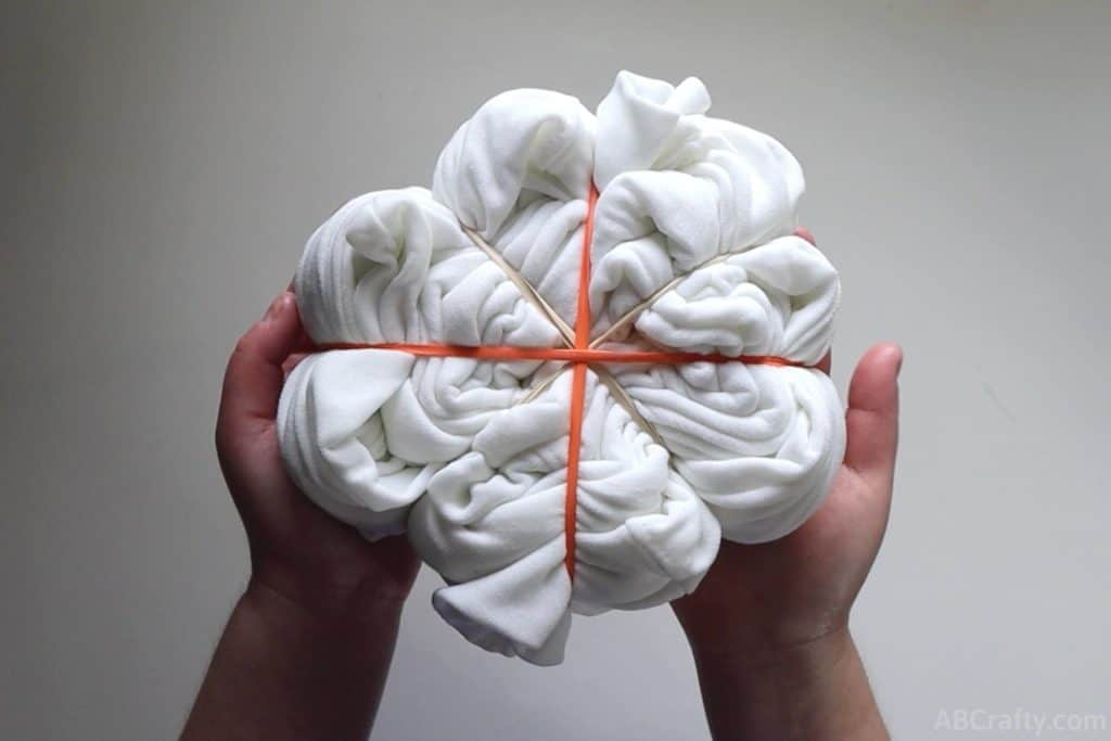 holding a white sweatshirt that's been wrapped with rubber bands