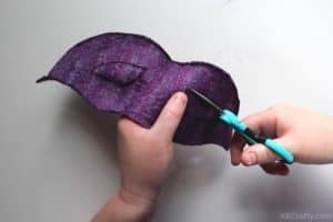 using tiny scissors to cut the outline of an eye hole for a masquerade mask out of handmade purple felt fabric