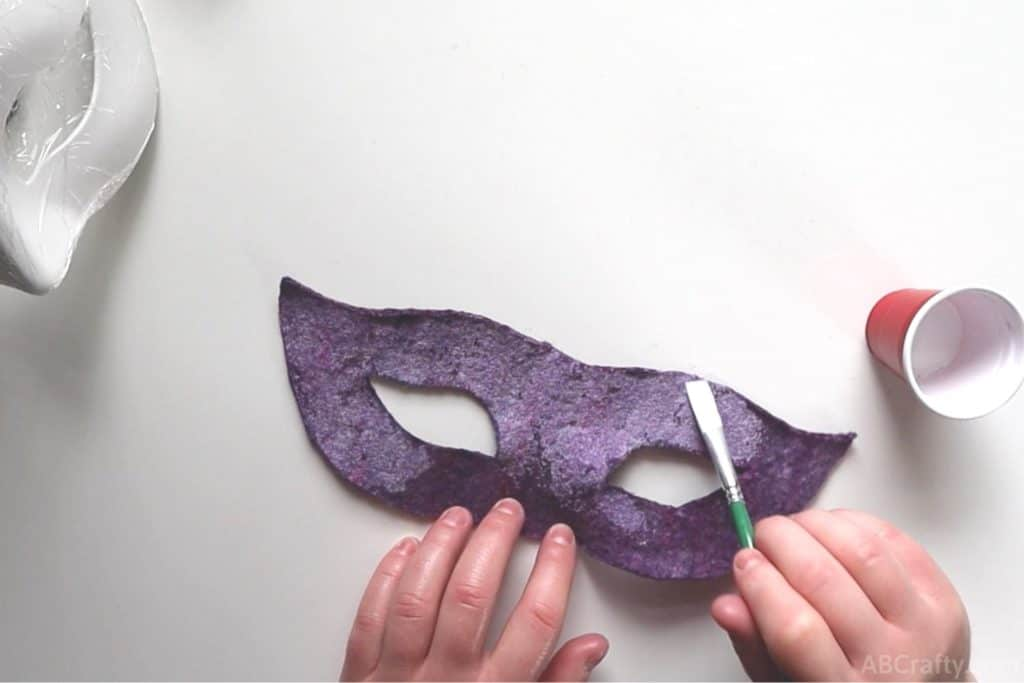 using a paint brush to pant the back of a wet felted carnival mask with Aleene's Fabric Stiffener Draping Liquid