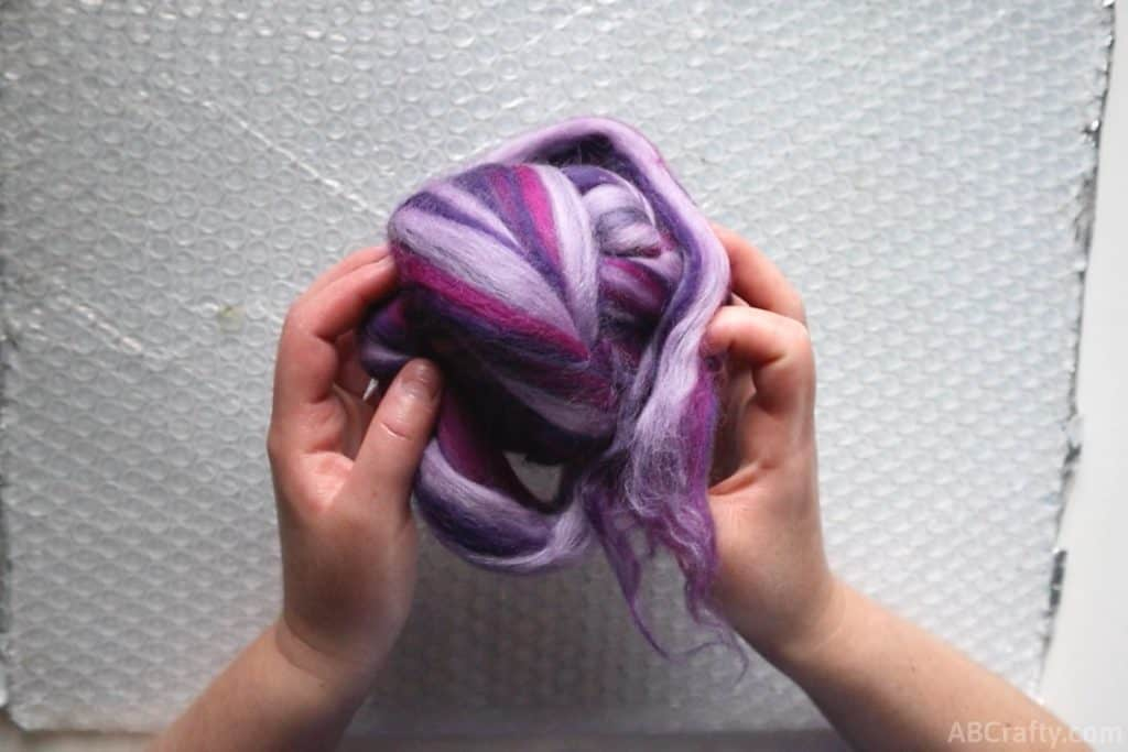 holding a ball of purple and pink wool roving