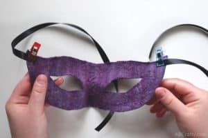 clips holding satin ribbon to the sides of handmade purple masquerade mask