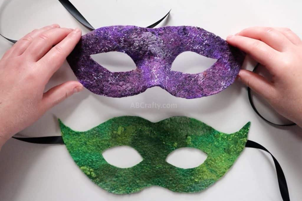 holding the finished handmade purple wet felted Venetian mask above a flat green felted masquerademask