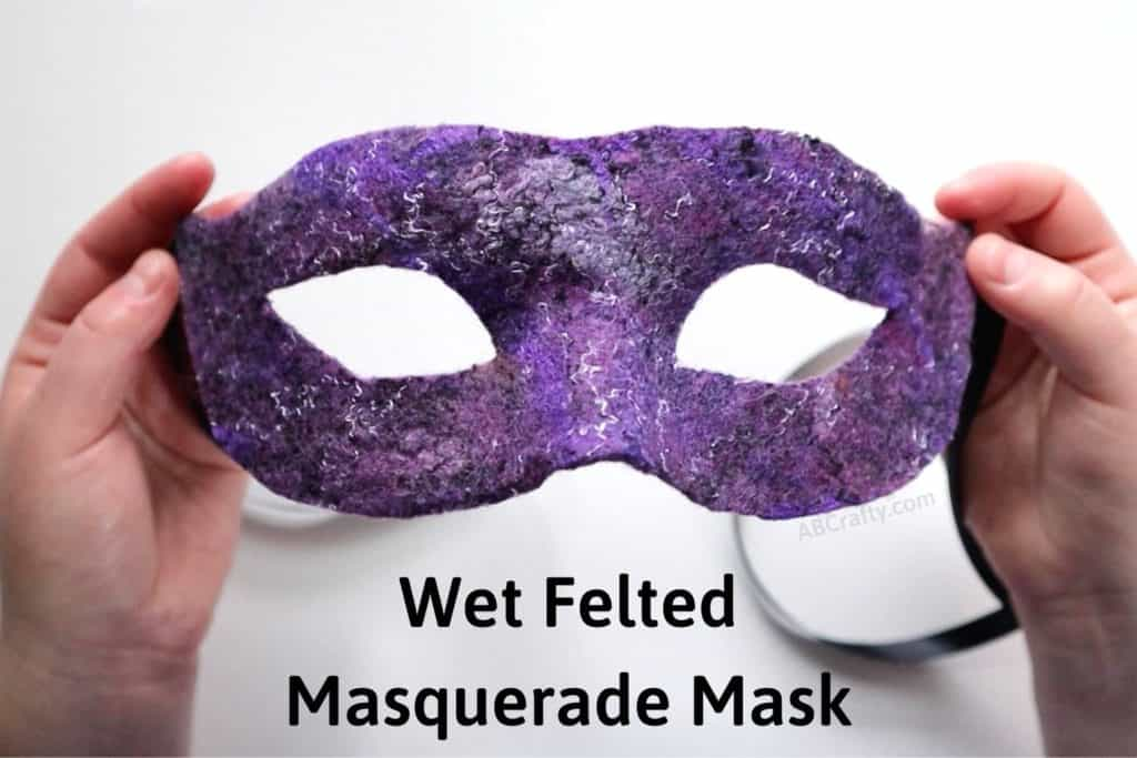 holding a purple silver and black Venetian mask with the title 'wet felted masquerade mask'