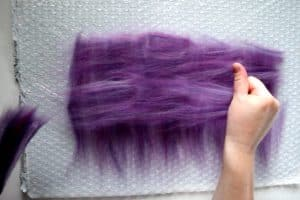 laying out purple wool fibers into perpendicular layers