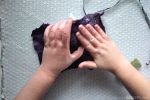 using hands to rub partially felted purple wool on top of a plastic mask