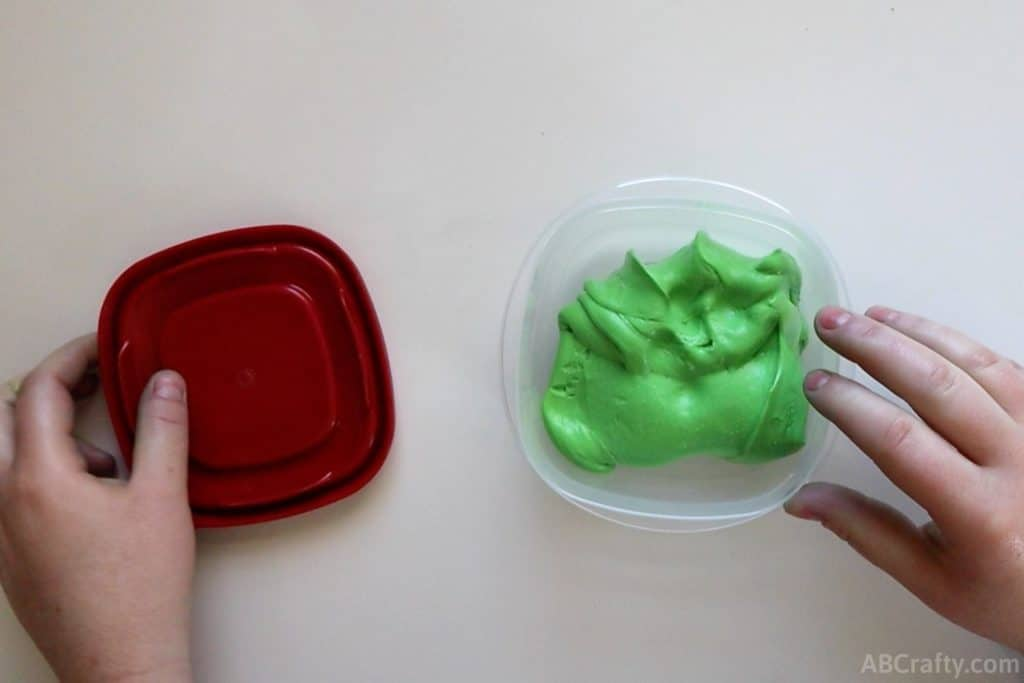 green goo in a plastic container with a red top to the side of it