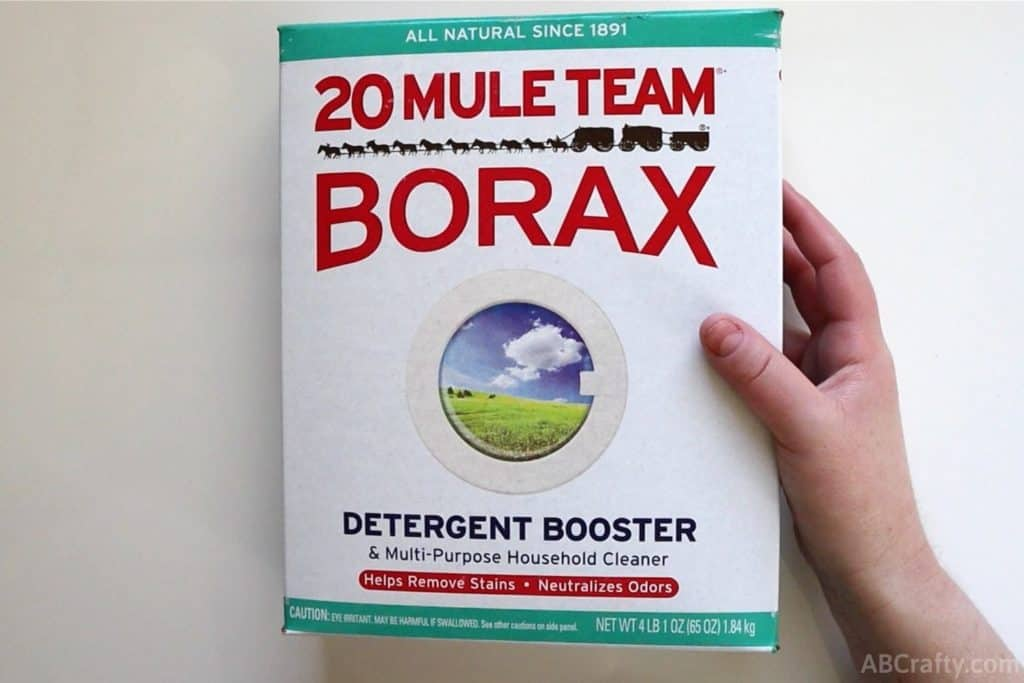 hand holding a box of 20 mule team borax detergent booster