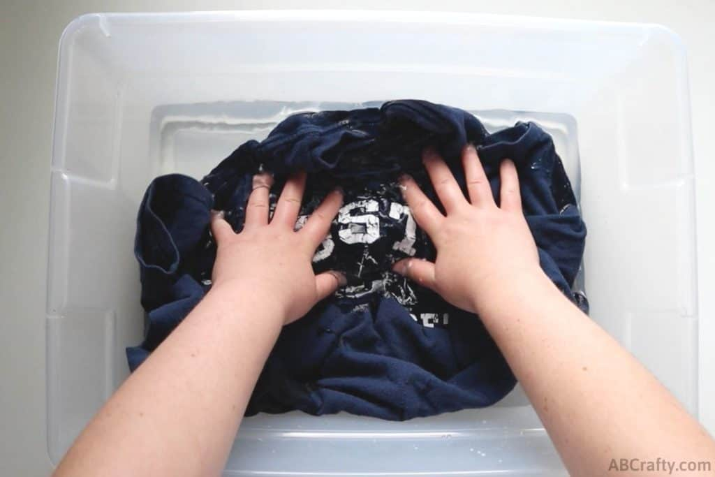 dunking a blue Boston shirt into a tub of water