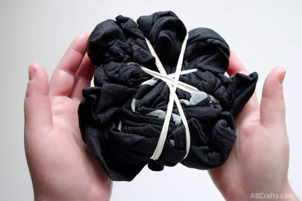 black t shirt bundled up and wrapped diagonally with rubber bands