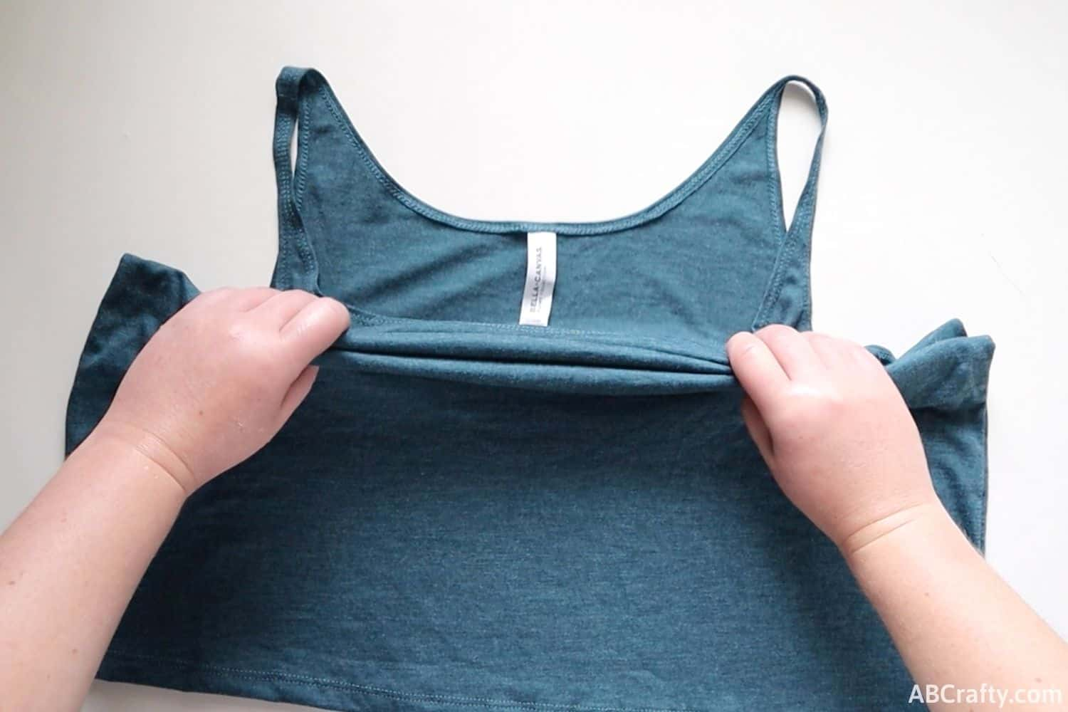 folding a blue tank top accordion style from the middle
