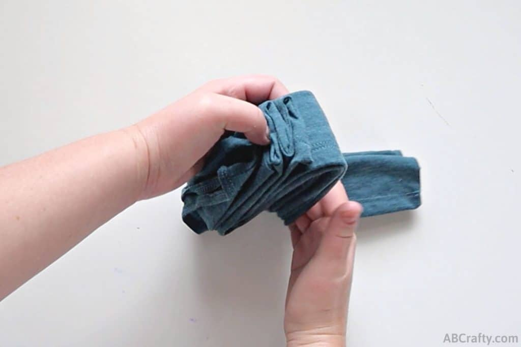 folding a folded blue tank top into thirds